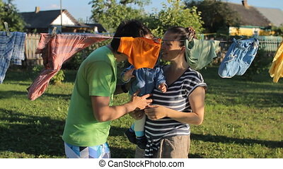Parents play with a cute baby boy. Near the beautiful baby clothes drying