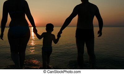 Parents playing ball with son in sea at sunset