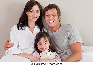 Parents posing with their daughter