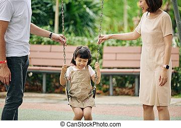 Parents pushing daughter on swing