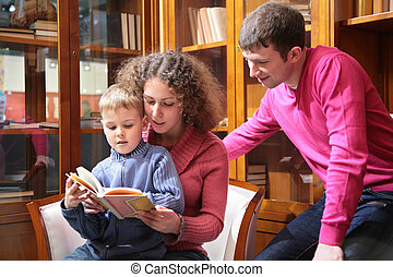 parents read book with son