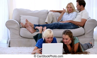 Parents relaxing on couch with chil
