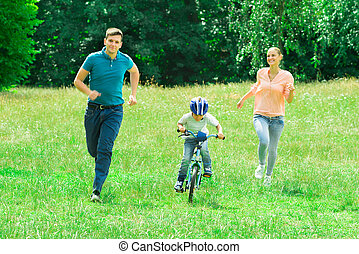 Parents Running With Their Son Riding A Bicycle