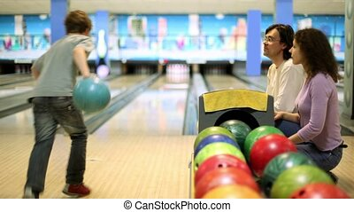 Parents sit and watch little boy throws bowling ball to beat skittles