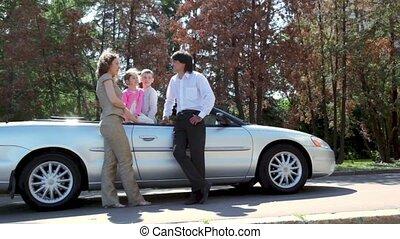 Parents speak near cabriolet and kids listen them inside car