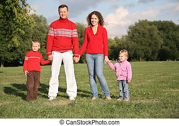 parents stand holding children for the hands