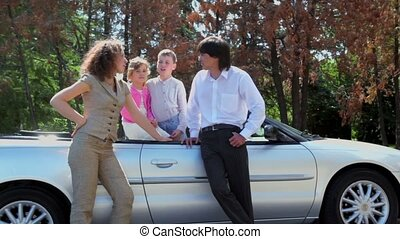 Parents stand near cabriolet and their kids inside cabriolet