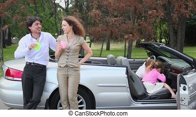 Parents stand with glasses near cabriolet, kids play in car