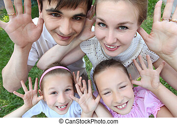 Parents stand with two children outdoor with opened palms,  top view