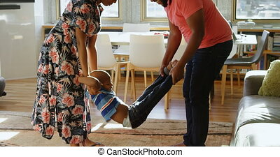 Side view of African american parents swinging their son in a comfortable home. They are smiling and having fun. 4k