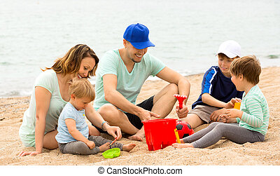 Parents talking and kids playing with sand