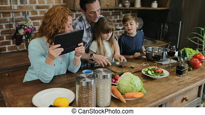Parents Teaching Children Cooking Together In Kitchen, Happy...