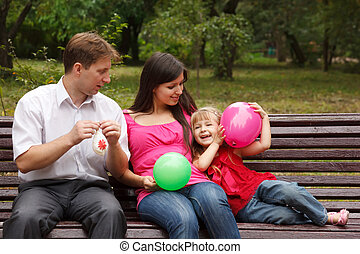 Parents together with daughter on bench in park in afternoon. Play with multi-coloured balloons.
