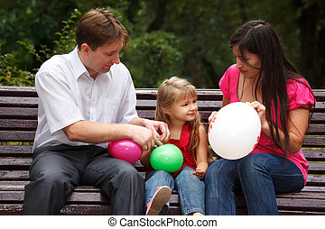 Parents together with daughter on bench in park in afternoon. In hands multi-coloured balloons.