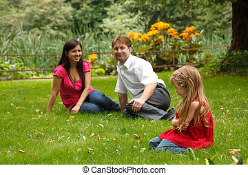 Parents together with little girl have rest in summer garden. Look at girl sitting on lawn.