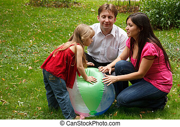 Parents together with little girl in summer garden. Play with big inflatable ball.