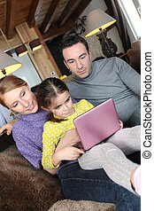 Parents using a pink laptop with their daughter