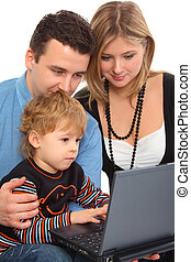 Parents whit son look on notebook