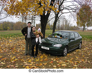 parents with baby and car
