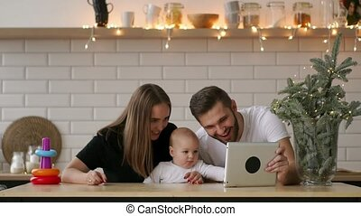 Parents with baby boy playing with digital tablet