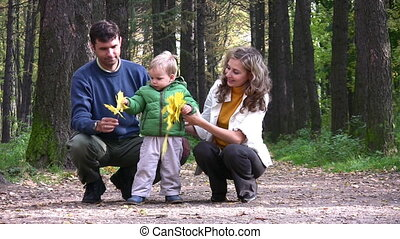 parents with boy with leaves in park