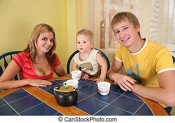 parents with  child drink tea at  table in  room 2