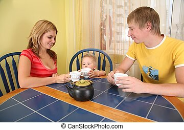 parents with child drink tea at table in room