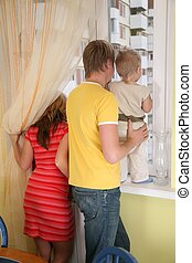 parents with child on hands look in window