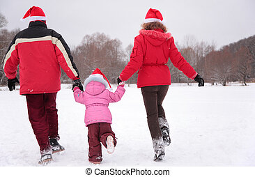 Parents with child run in park in winter from back