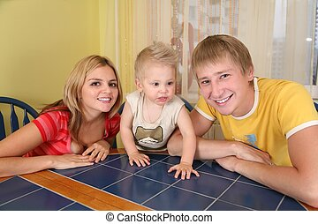parents with child sit at table