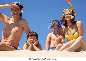 Parents with children in underwater masks sit on sand