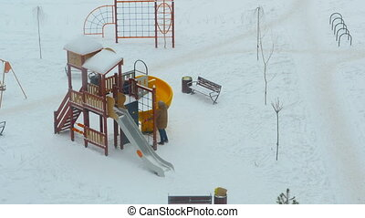 parents with children play on the playground in winter time lapse