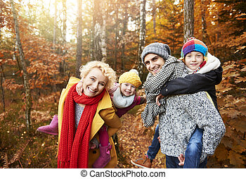 Parents with children playing in forest