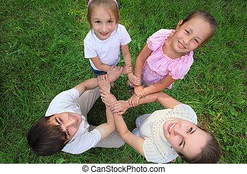 Parents with children stand having joined hands crosswise,  top view