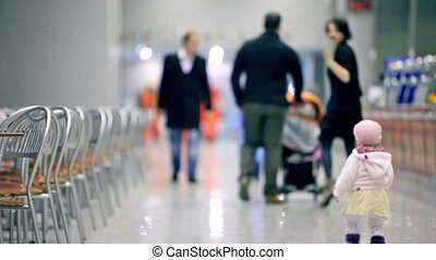 Parents with kids walk in cafe, unfocused view