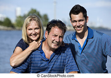 parents with son - family of three posing together close to...