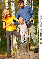 Parents with son in forest in autumn