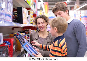 Parents with son in toy`s shop