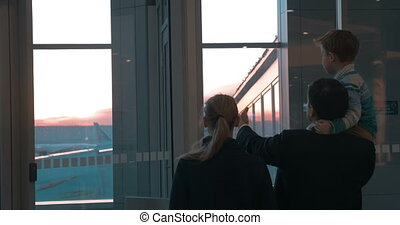 Parents with son looking at planes through the window