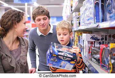 Parents with son with toy in shop, focus on father