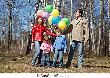 Parents with the daughter and the son walk in park with balloons.