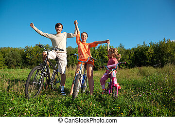 Parents with the daughter on bicycles in park a sunny day. Have joyfully thrown up hands.