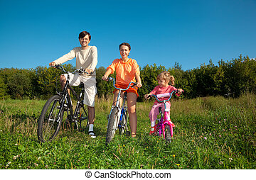 Parents with the daughter on bicycles in park a sunny day.