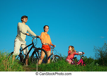 Parents with the daughter on bicycles, in the summer evening.