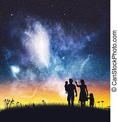 Parents with their children on a night sky.