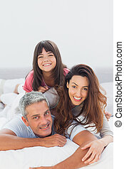 Parents with their daughter lying o