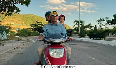Parents with their little kid riding motorcycle on sunny city street