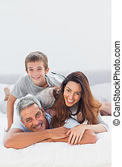 Parents with their son lying on bed