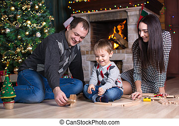 Parents with their son play with model railway near christmas tree in room