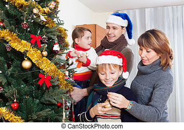 Parents with two children decorating Christmas tree